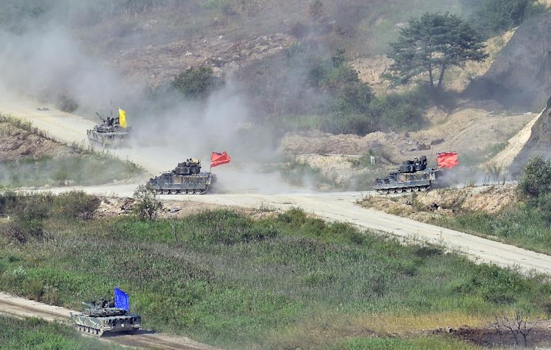 South Korean K1A1 tanks and US M2 Bradley infantry fighting vehicles (C-orange) participate in a joint live firing drill with the US, at the Seungjin Fire Training Field in Pocheon, on August 28, 2015 (AFP Photo/Jung Yeon-Je)