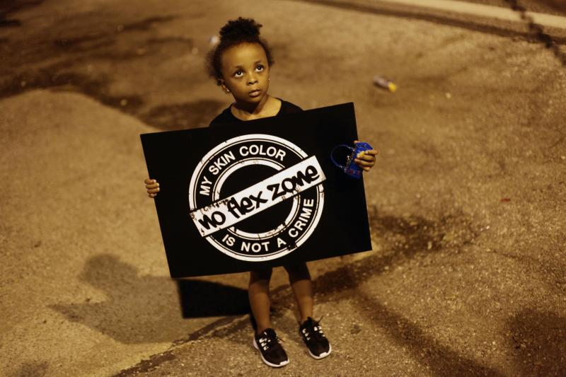 A girl holds a sign as she protests the shooting of Michael Brown August 21, 2014 in Ferguson, Missouri (AFP Photo/Joshua Lott)