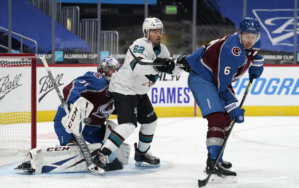 San Jose Sharks right wing Kevin Labanc, center, distracts Colorado Avalanche defenseman Erik Johnson, right, as the puck slips wide of the net past goaltender Philipp Grubauer during the second period of an NHL hockey game Tuesday, Jan. 26, 2021, in Denver. (AP Photo/David Zalubowski)