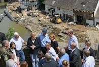 The veteran German leader listened to the accounts of residents where the swollen Ahr river swept away houses and left debris piled high in the streets