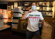 Benny Yun, owner of Yang Chow restaurant fills take-out orders in Los Angeles, Thursday, Dec. 17, 2020. Bigotry toward Asian Americans and Asian food has spread steadily alongside the coronavirus in the United States. Yun said even though his businesses have survived the pandemic, they get prank calls almost daily asking if they have dog or cat on the menu or impersonating a thick Asian accent. (AP Photo/Damian Dovarganes)