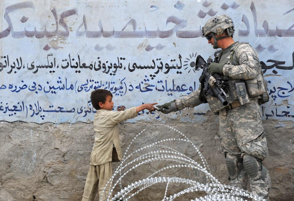 <p>US soldier  presents a gift to an Afghan child during a patrol at Khogiani in Langarhar in 2010</p> (AFP)
