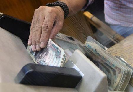 An employee counts Egyptian pounds in a foreign exchange office in central Cairo
