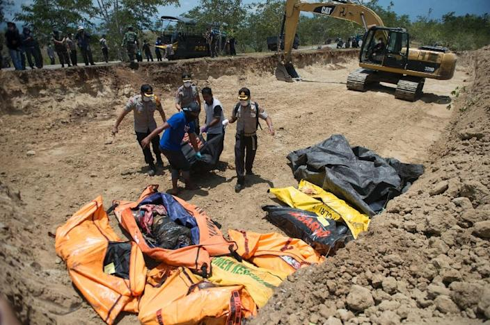 Rescue officials have been keen to bury victims in mass graves to stop the spread of disease (AFP Photo/BAY ISMOYO)