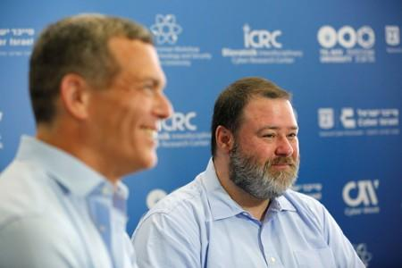 Derek Vadala, the chief executive of a joint venture between Moody's Corp and Israeli cyber group Team8, and Nadav Zafrir, CEO of Team8, smiles during an interview with Reuters at a cyber conference at Tel Aviv University
