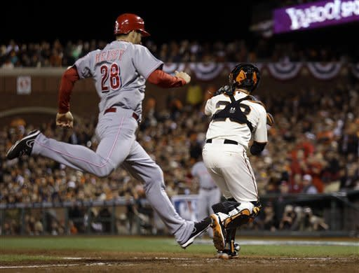 Cincinnati Reds' Chris Heisey scores on a double by Jay Bruce as San Francisco Giants catcher Buster Posey looks for the throw, during Game 2 of the National League division baseball series in San Francisco, Sunday, Oct. 7, 2012. (AP Photo/Marcio Jose Sanchez)