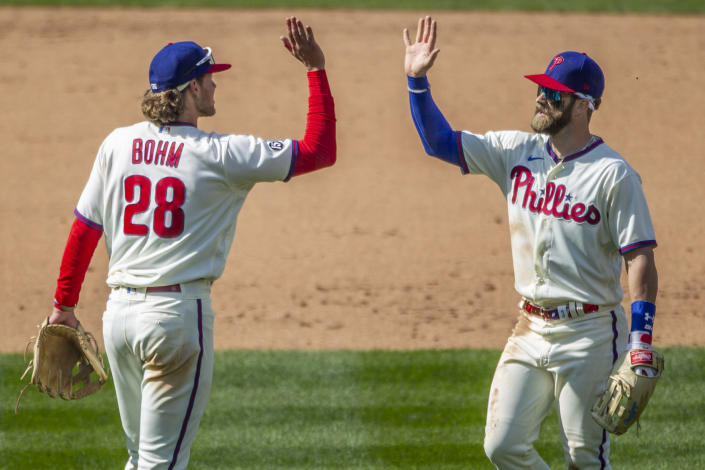 Philadelphia Phillies third baseman Alec Bohm, left, and right fielder Bryce Harper, right, high five after their team defeated the Atlanta Braves in a baseball game, Sunday, April 4, 2021, in Philadelphia. (AP Photo/Laurence Kesterson)