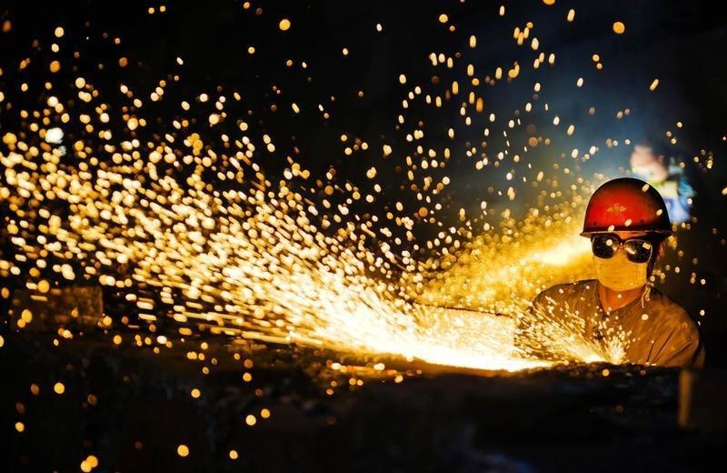 A worker wearing protective glasses welds steel products at a heavy equipment manufacturing factory in Luoyang