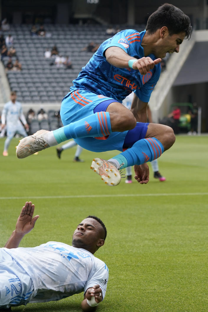 New York City FC forward Andres Jasson, top, jumps over Los Angeles FC defender Diego Palacios (12) during the first half of an MLS soccer game Saturday, May 29, 2021, in Los Angeles. (AP Photo/Ashley Landis)