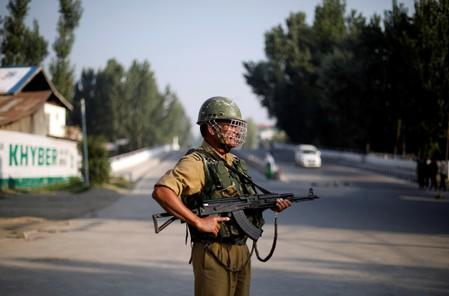 An Indian security personnel stands guard on a deserted road during restrictions after scrapping of the special constitutional status for Kashmir by the Indian government, in Srinagar