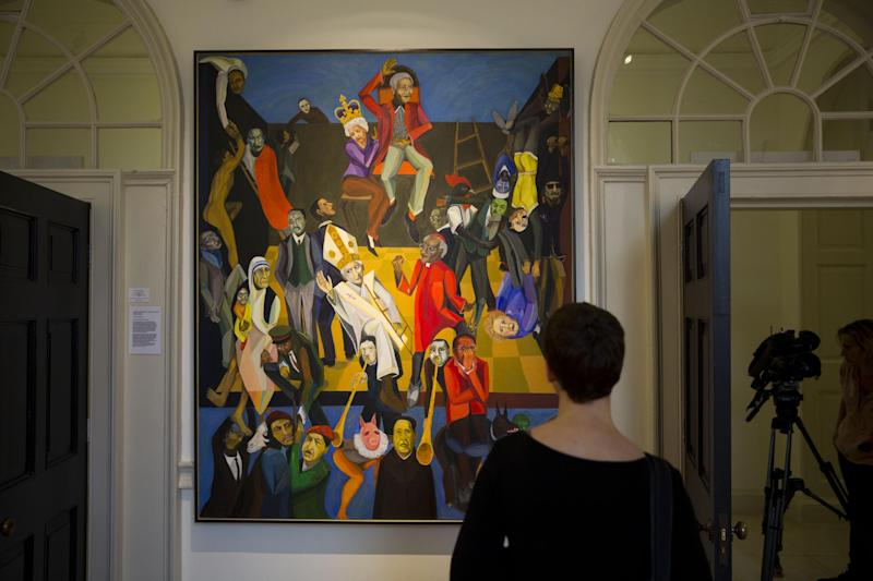 """A woman looks at Zimbabwean artist Richard Mudariki's """"The Last Judgement"""", acrylic on canvas, which features in the """"1:54 Contemporary African Art Fair"""" at Somerset House in London, Thursday, Oct. 17, 2013. African tribal art has long been treasured by wealthy Western collectors, but increasingly the continent's contemporary art scene is the one making its presence felt at museums, auction houses and art fairs. London now has four galleries focused on African contemporary art, three of them opening in the past three years. (AP Photo/Matt Dunham)"""