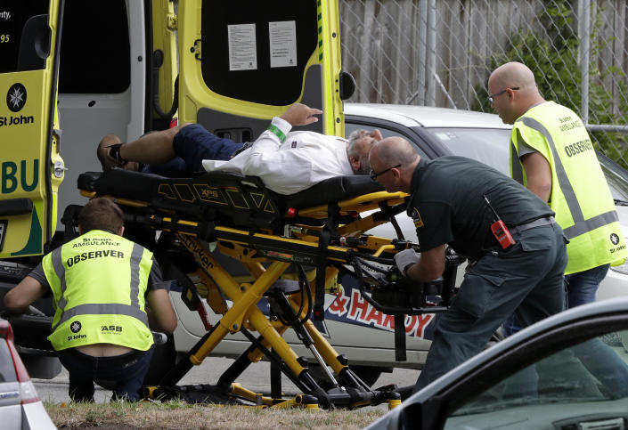 FILE - In this March 15, 2019, file photo, ambulance staff take a man from outside a mosque in central Christchurch, New Zealand. More than 60 survivors and family members will confront the New Zealand mosque gunman during the four-day sentencing starting Monday, Aug. 24, 2020. Twenty-nine-year-old Australian Brenton Harrison Tarrant has pleaded guilty to 51 counts of murder, 40 counts of attempted murder and one count of terrorism in the worst atrocity in the nation's modern history.(AP Photo/Mark Baker, File)