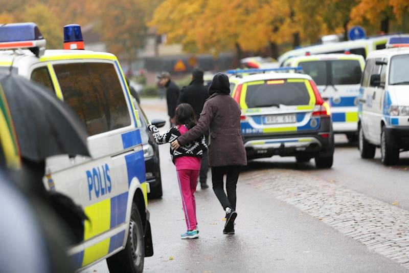 A pupil and her parent leave a primary and middle school in Trollhattan, southwestern Sweden, on October 22, 2015, after an attack by a man with a sword (AFP Photo/Bjorn Larsson Rosvall)