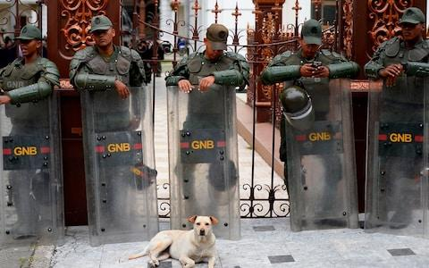 Members of the Venezuelan National Guard stand outside the National Assembly in Caracas - Credit: Matias Delacroix / AFP