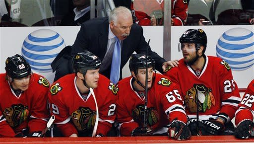 FILE - In this Jan. 27, 2013, file photo, Chicago Blackhawks head coach Joel Quenneville talks to Viktor Stalberg (25) as Patrick Kane (88), Bryan Bickell (29) and Andrew Shaw (65) sit by late in the third period of an NHL hockey game against the Detroit Red Wings in Chicago. Forward Patrick Sharp says Quenneville has played a key role in the team's record-breaking start. Chicago has at least one point in each of its first 19 games and puts the streak on the line Thursday night in St. Louis. (AP Photo/John Smierciak, File)