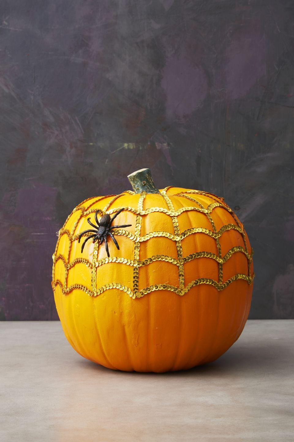 """<p>Using hot glue, place strings of sequins going about halfway down the pumpkin. Next, go horizontal with curved lines to complete the cobweb. A spider is optional but encouraged!</p><p><a class=""""link rapid-noclick-resp"""" href=""""https://www.amazon.com/Expo-International-20-Yard-Starlight-Hologram/dp/B00G02ZTA8/?tag=syn-yahoo-20&ascsubtag=%5Bartid%7C10055.g.1714%5Bsrc%7Cyahoo-us"""" rel=""""nofollow noopener"""" target=""""_blank"""" data-ylk=""""slk:SHOP SEQUINS"""">SHOP SEQUINS</a><br></p>"""