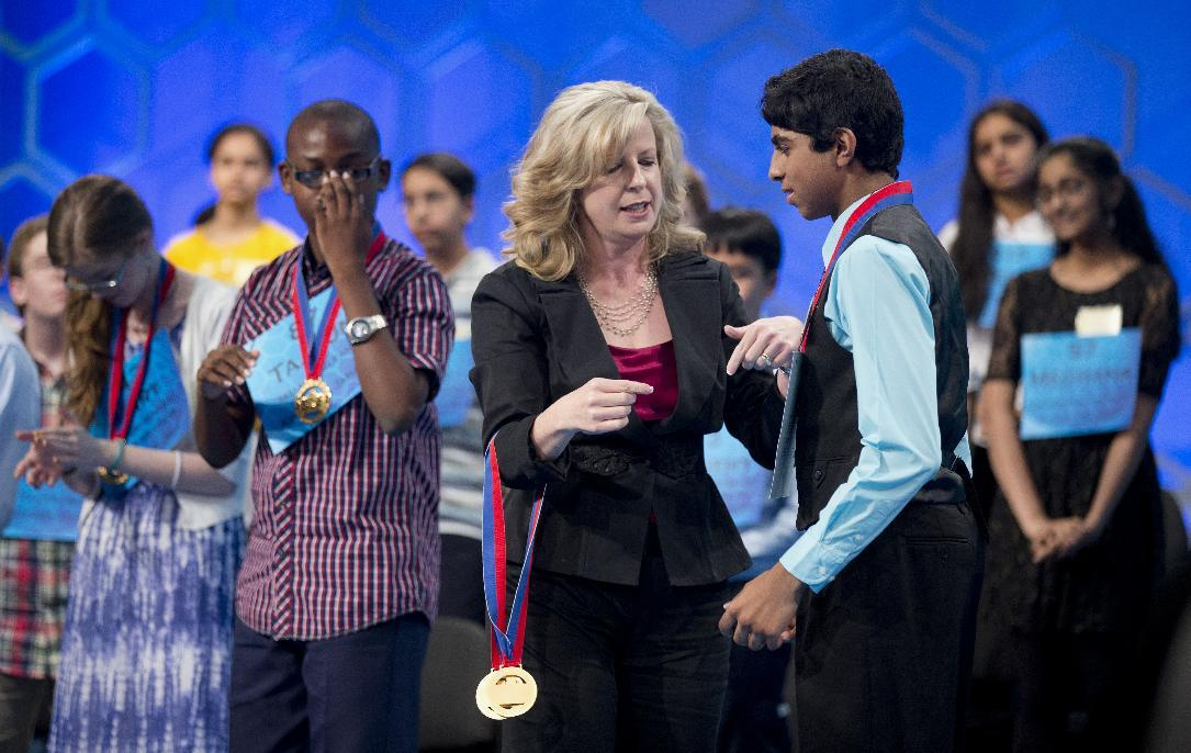 Ansun Sujoe, right, 13, from Fort Worth, Texas, is congratulated by Paige Kimble, executive director of the Scripps National Spelling Bee, after being awarded a medal and making it to the finals of the Scripps National Spelling Bee, Thursday, May 29, 2014, at National Harbor in Oxon Hill, Md. Standing on the from left are, finalists Mary Horton, 13, of West Melbourne, Fla., Tajaun Gibbison, 13, of Mandeville, Jamaica. (AP Photo/Manuel Balce Ceneta)
