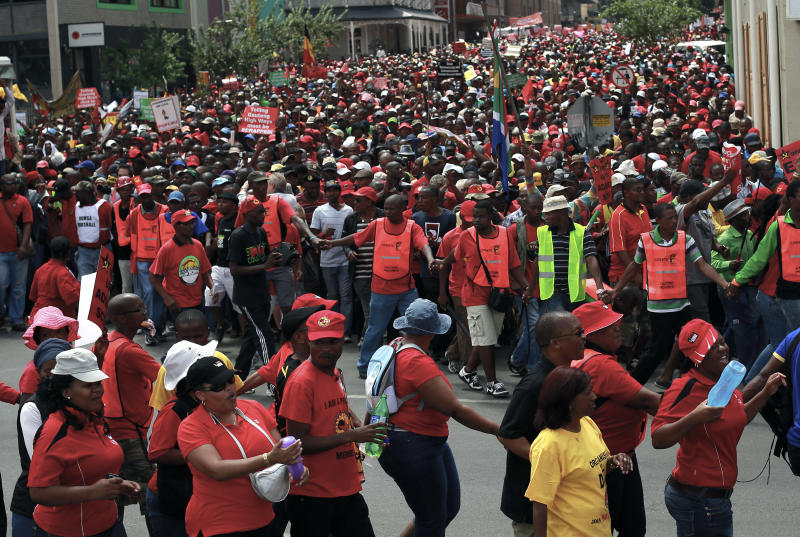 South African protestors march downtown Johannesburg, South Africa, Wednesday March 7, 2012. Tens of thousands of South Africans marched peacefully through their main cities in a protest organized by the country's biggest trade union federation against economic decisions made by the governing African National Congress. The Congress of South African Trade Unions, known as COSATU, is a close ally of the ANC, but often among its sharpest critics. (AP Photo/Jerome Delay)