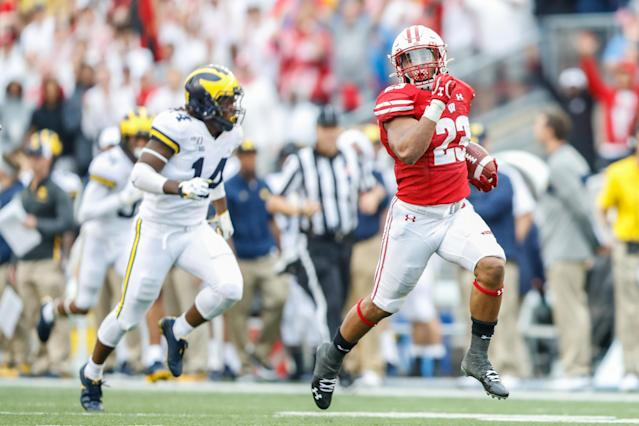 Wisconsin running back Jonathan Taylor runs past Michigan defensive back Josh Metellus to score a touchdown on Saturday. (Getty)