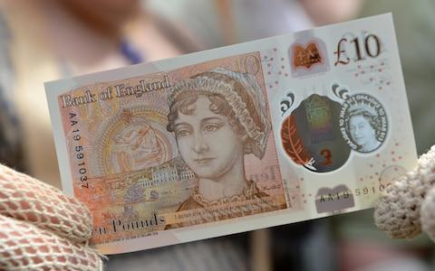 People in period costume pose with the new £10 note featuring Jane Austen - Credit: REUTERS/Chris J Ratcliffe