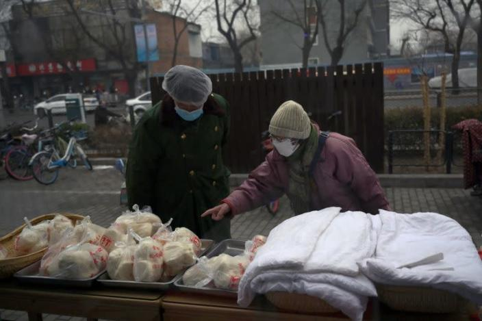 Woman wearing a face mask buys food from a stall set up by a restaurant outside its outlet in Beijing