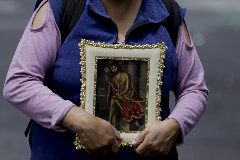 A woman holds a religious image during a protest against President Lenín Moreno's decision to end subsidies that led to a sharp increase in fuel prices, in Quito, Ecuador, Oct. 8, 2019. (Photo: Fernando Vergara/AP)