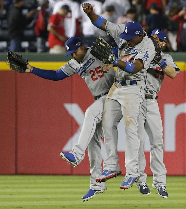 Los Angeles Dodgers left fielder Carl Crawford (25) Los Angeles Dodgers third baseman Jerry Hairston Jr. (6) and Los Angeles Dodgers second baseman Skip Schumaker (55) celebrate after Game 1 of the National League Divisional Series against the Atlanta Braves, Friday, Oct. 4, 2013, in Atlanta. The Dodgers won 6-1. (AP Photo/John Bazemore)