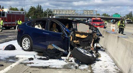 Rescue workers attend the scene where a Tesla electric SUV crashed into a barrier on U.S. Highway 101 in Mountain View