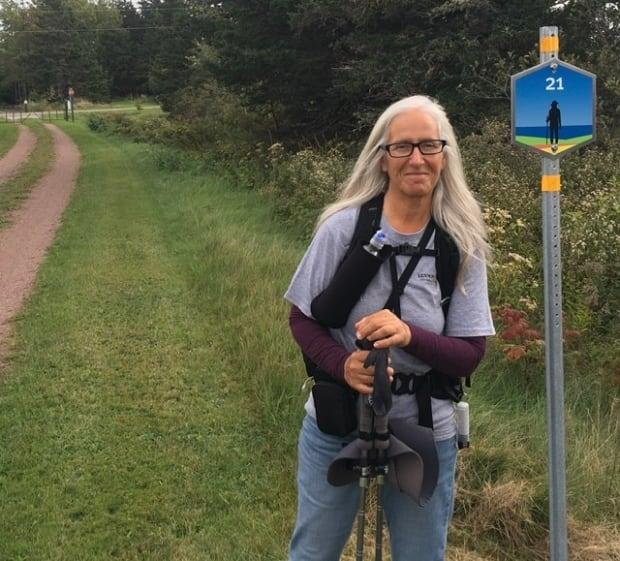 Christine Renaud poses by the last marker on her 714 km walk across P.E.I. to raise money for addiction services. (Submitted by Christine Renaud - image credit)