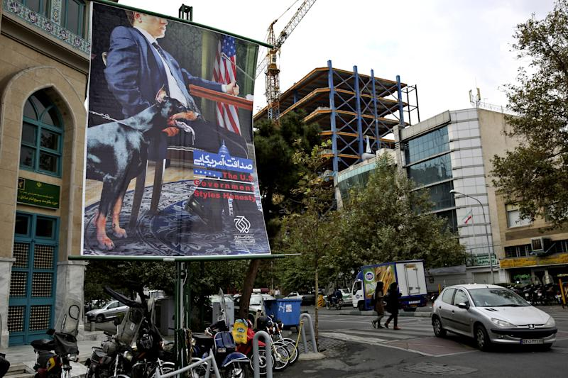 """A poster depicting an American negotiator wearing a suit jacket and tie at a negotiating table and a dog to his side is displayed in Palestine square, Tehran, Iran, Sunday, Oct. 27, 2013. Iranian President Hassan Rouhani has described his outreach to the U.S. as part of a """"new era'' and a chance to put the nuclear standoff with the West to rest. (AP Photo/Ebrahim Noroozi)"""