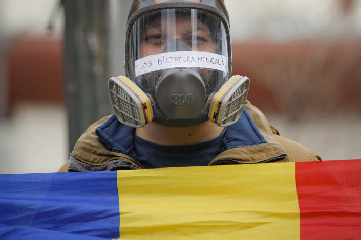 "A man wears a gas mask with the text ""Down the Medical Dictatorship"" on it, during a protest against the COVID-19 pandemic restrictions in Bucharest, Romania, Saturday, April 3, 2021. Hundreds of anti-restriction protesters took to the streets in several cities across Romania. (AP Photo/Vadim Ghirda)"