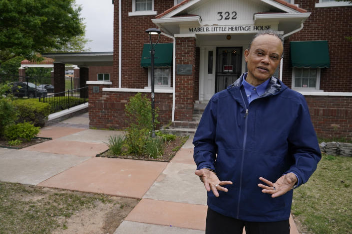 """Tulsa historian Hannibal Johnson stands in front of the Mabel B. Little Historical House Tuesday, April 27, 2021, in the Greenwood area of Tulsa, Okla. After Oklahoma became a state, the first law approved was a Jim Crow statute requiring segregation of rail cars and depots. """"Oklahoma, in many ways although arguably not a Southern state in terms of racial policy, began to mimic the Deep South,"""" Johnson says. (AP Photo/Sue Ogrocki)"""