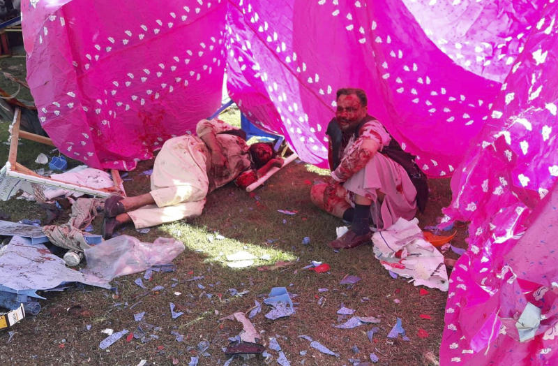 Wounded men sit in a tent following multiple explosions in Lashkar Gah city of Helmand province, southern Afghanistan, Saturday, Mar. 23, 2019. An Afghan official says that at least three have been killed in twin bomb explosions occurred during the Farmer's Day ceremony in southern Helmand province. (AP Photo/Abdul Khaliq)