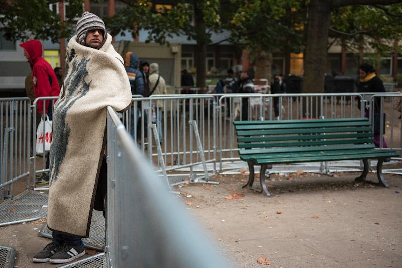 An immigrant shelters from the cold in a blanket outside the Office of Health and Social Affairs in Berlin (AFP Photo/Odd Andersen)