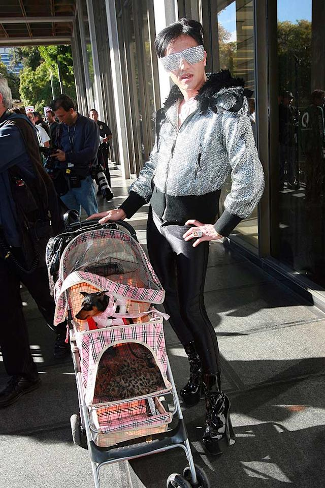 """Speaking of train wrecks, D-list decorator Bobby Trendy took his petite pooch for a stroll in downtown LA while wearing yet another scary ensemble consisting of a bedazzled hoodie, skintight trousers, and patent leather platform heels. Turner/<a href=""""http://www.splashnewsonline.com"""" target=""""new"""">Splash News</a> - March 5, 2009"""