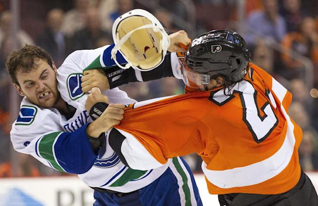 Vancouver Canucks' Zack Kassian, left, loses his helmet as he fights with Philadelphia Flyers' Luke Schenn, right, during the first period of an NHL hockey game, Tuesday, Oct. 15, 2013, in Philadelphia. (AP Photo/Chris Szagola)