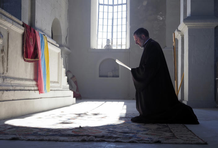 A priest prays in the Holy Savior Cathedral, damaged by shelling by Azerbaijan's artillery during a military conflict in Shushi, the separatist region of Nagorno-Karabakh, Saturday, Oct. 24, 2020. The heavy shelling forced residents of Stepanakert, the regional capital of Nagorno-Karabakh, into shelters, as emergency teams rushed to extinguish fires. Nagorno-Karabakh authorities said other towns in the region were also targeted by Azerbaijani artillery fire. (AP Photo)