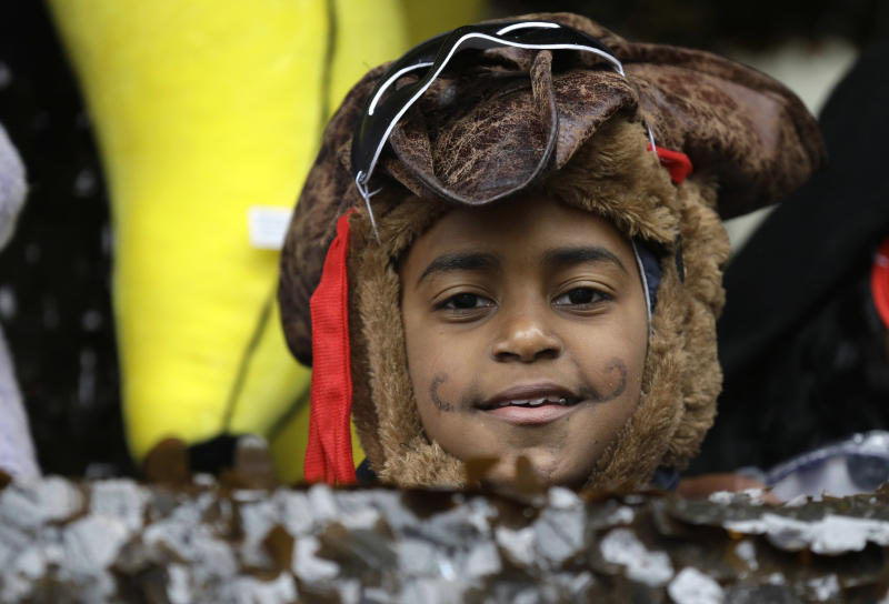 A child in costume peers from a float in the Krewe of Elks during Mardi Gras in New Orleans, Tuesday, March 4, 2014. Rain and unusually cold temperatures kept most of the normally massive and festive crowds away. (AP Photo/Gerald Herbert)