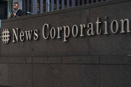 File photo of a passer-by in front of the News Corporation building in New York