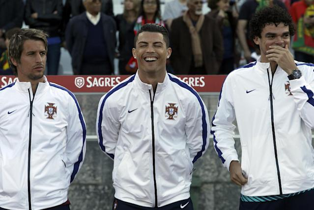 Portugal's Cristiano Ronaldo, centre, laughs with teammates Fabio Coentrao, left, and Pepe prior a friendly soccer match between Portugal and Greece at the National stadium, in Oeiras, near Lisbon, Saturday, May 31, 2014. The game was a warm-up match for both teams ahead the World Cup in Brazil. The match ended in a 0-0 draw. (AP Photo/Francisco Seco)