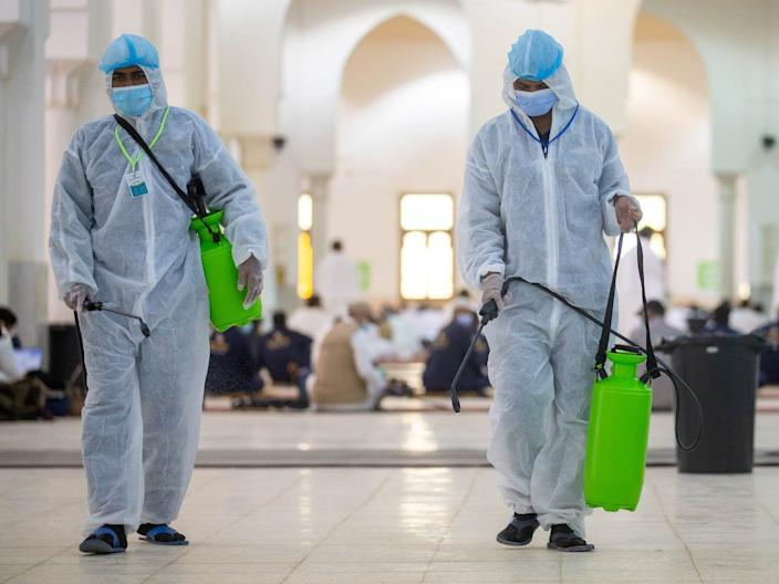 Health workers wearing personal protective equipment (PPE) disinfect the floor as Muslim pilgrims pray inside Namira Mosque in Arafat to mark Haj's most important day, Day of Arafat, on July 30, 2020.