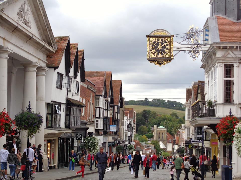 Guildford is a picturesque market and university town in Surrey. this photo shows the town hall clock and the steep slope of the high street going towards the River Wey.