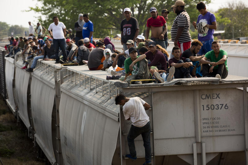 Central American migrants wait on the top of a parked train during their journey toward the US-Mexico border in Ixtepec, Oaxaca state, Mexico, Tuesday, April 23, 2019. The once large caravan of about 3,000 people was essentially broken up by an immigration raid on Monday, as migrants fled into the hills, took refuge at shelters and churches or hopped passing freight trains. (AP Photo/Moises Castillo)