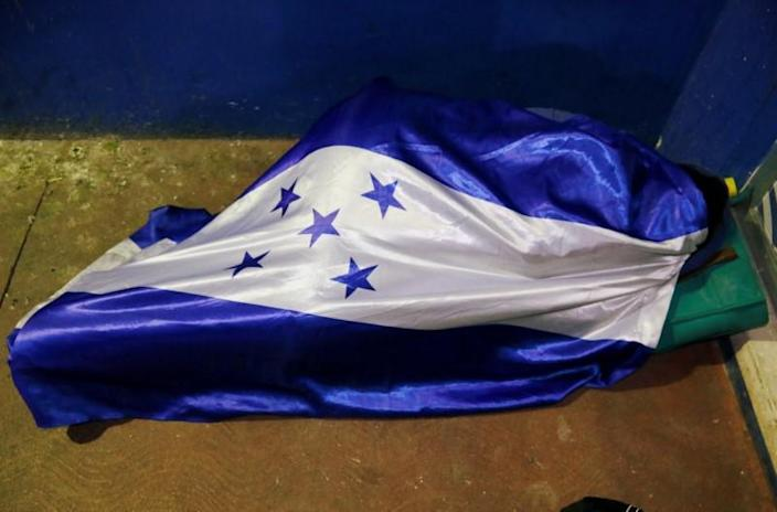 A person, part of a caravan of migrants heading toward the United States, rests covered in a Honduras' national flag, at the border between Honduras and Guatemala in Agua Caliente