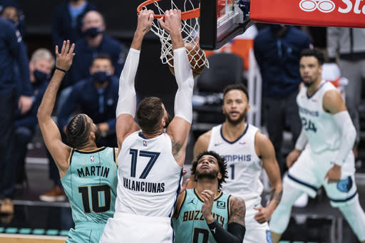Memphis Grizzlies center Jonas Valanciunas (17) dunks over Charlotte Hornets forward Caleb Martin (10) and forward Miles Bridges (0) during the second half of an NBA basketball game in Charlotte, N.C., Friday, Jan. 1, 2021. (AP Photo/Jacob Kupferman)