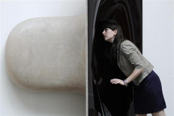 An employee poses with artist Anish Kapoor's untitled sculpture at the press view of the Summer Exhibition 2011 at the Royal Academy of Arts in London, June 2, 2011.