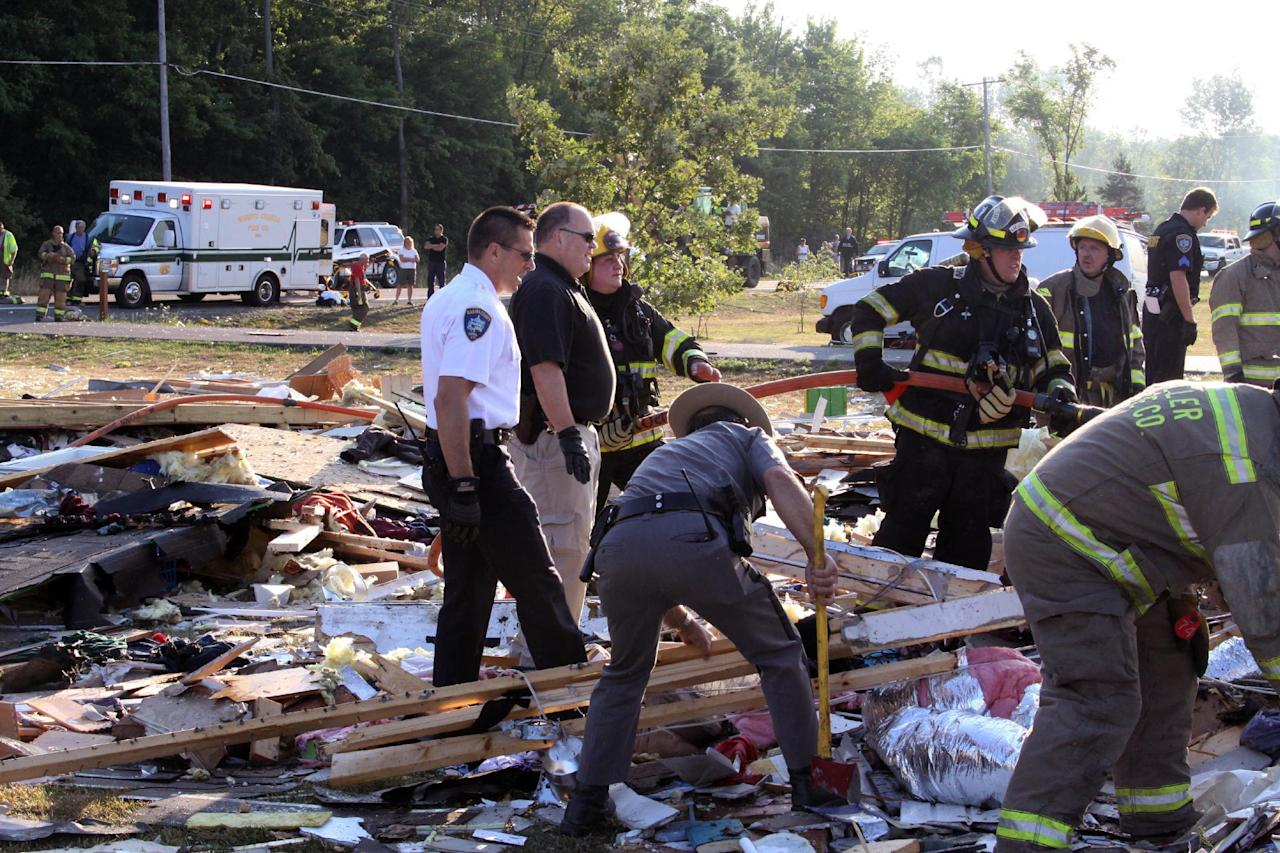 Emergency personnel work the scene around a house after an explosion on Tuesday, July 24, 2012 in Wilson, N.Y. The blast leveled the house killing a girl and injuring her parents and two siblings, authorities said. Sarah Johnson's body was found in the debris at the rear of the home, Niagara County Undersheriff Michael Filicetti said. Authorities weren't sure of her age but believe she was between 12 and 14. Filicetti said her parents and two siblings were blown clear and were found in the front yard by the first deputy to arrive on the scene. All four were being treated at a Buffalo hospital for serious injuries, he said. (AP Photo/Stephen M Wallace)