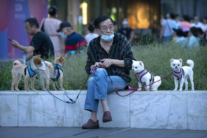 A man wearing a face mask to protect against COVID-19 sits with dogs on leashes near a neighborhood with a suspected coronavirus case in Beijing, Wednesday, Sept. 15, 2021. China tightened lockdowns and increased orders for mass testing in cities along its east coast Wednesday amid the latest surge in COVID-19 cases. (AP Photo/Mark Schiefelbein)