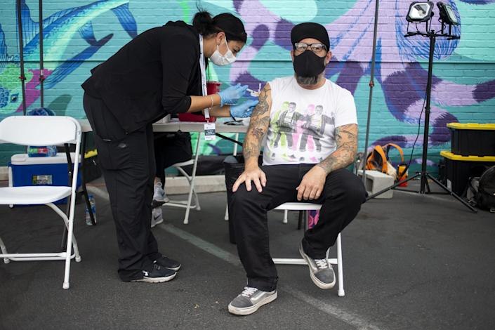 Justin McCawley receives a COVID-19 vaccine at a pop-up site in the parking lot next to Antigone Books in Tucson, Ariz., on May 20, 2021.