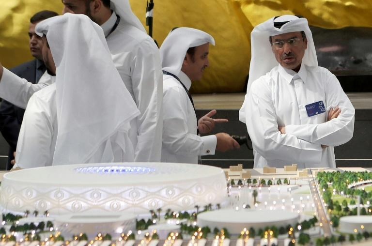 Qatari delegates look at a model of Al-Thumama stadium where two contractors have tested positive for COVID-19 (AFP Photo/KARIM JAAFAR)